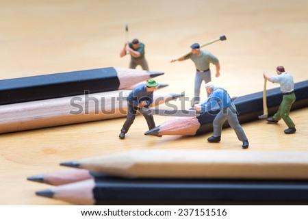 Small carpenter with handsaw cutting the pencil on wooden table - stock photo