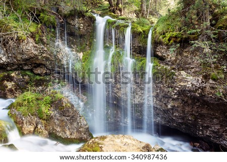 small cascade of a stream in the forest - stock photo