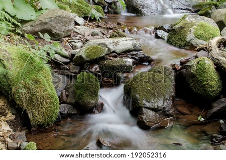 Small cascade on the mountain stream - stock photo