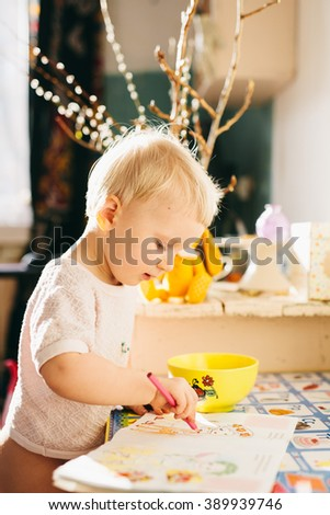 Small caucasian blonde baby girl  play & draw at the table and on the table. playing at home - stock photo