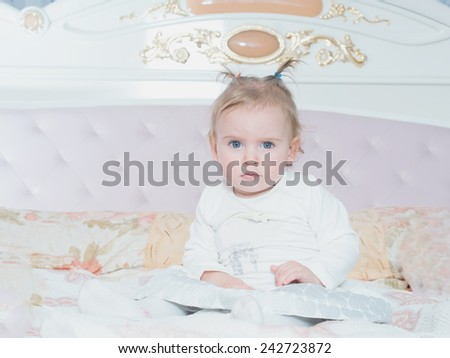 Small caucasian child girl sitting on the bed