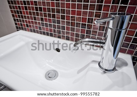 small ceramic hand wash basin with mosaic tiles - stock photo