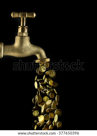 Small change flowing down from golden tab on black background - stock photo