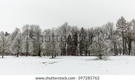 Small chapel between trees in a snowy landscape - stock photo