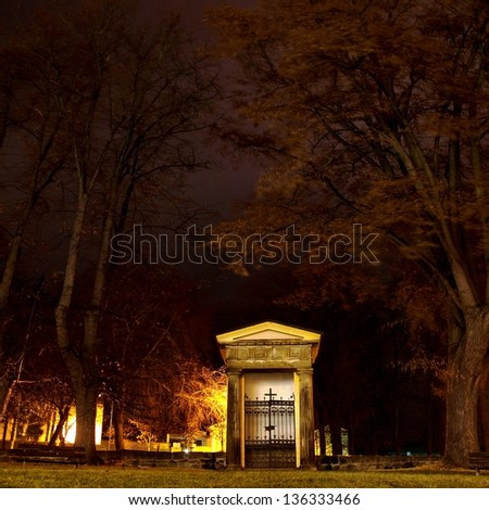 Small chapel in front of graveyard in the windy night. - stock photo