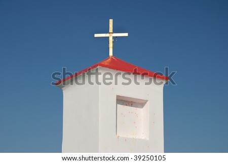 Small chapel with a red roof against the dark blue sky