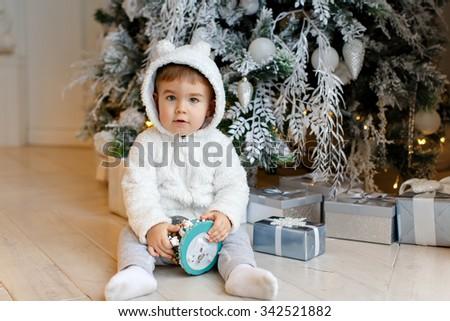 Small charming baby boy clothing polar bear cub sits near a Christmas fir-tree, holding a ball in the interior of the house - stock photo