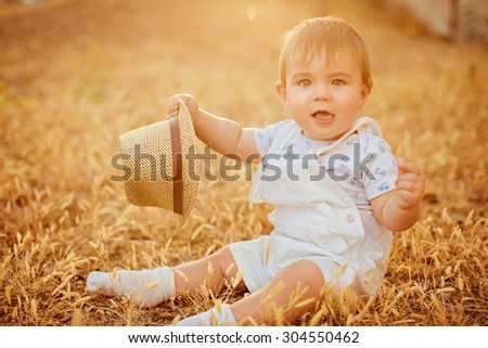 Small charming chubby little boy in a white suit holding a hat , sitting in a field in the spikelets in the warm rays of the setting sun in the summer - stock photo