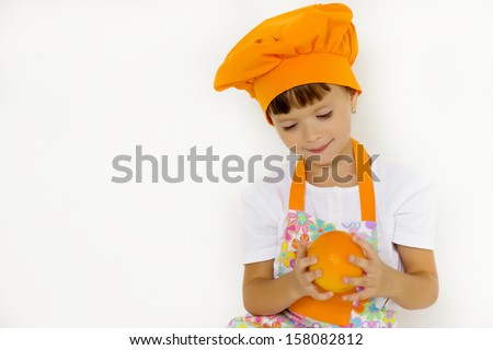 small chef holding an orange in her hand, soft focus - stock photo