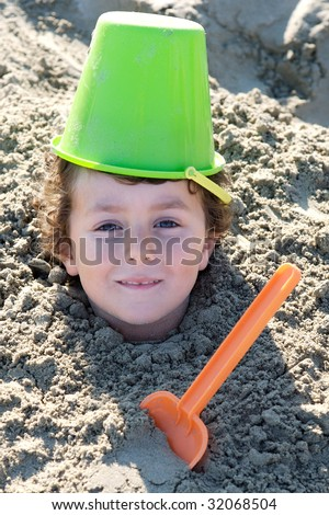 Small child buried in the sand of the beach - stock photo