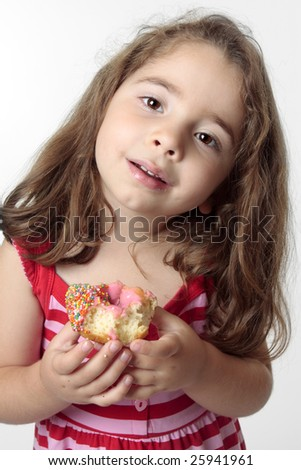 Small child eating a pink iced  doughnut.  She has messy fingers.