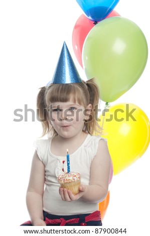 small child excited about the cup cake in her hand. Looks like she is about to blow the candle out