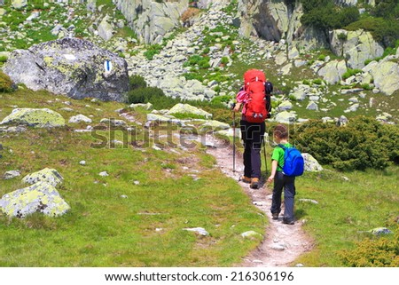 Small child follows his mother while carrying backpacks on on sunny mountain trail - stock photo