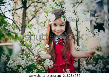 small child girl looking through cherry flowers