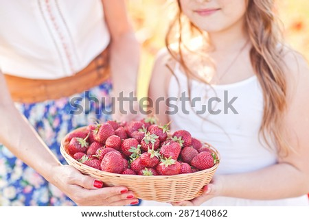 Small child hand with basket of strawberry. Summer mood - stock photo