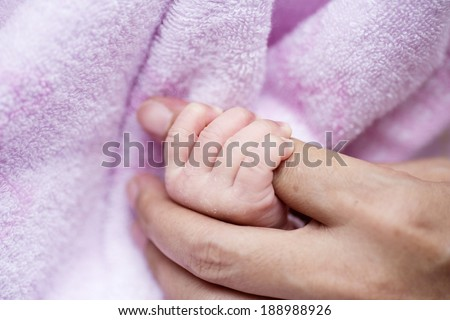 small child holding the handle of the mother - stock photo
