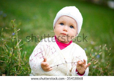 Small child in a grass. Looks in a camera. - stock photo