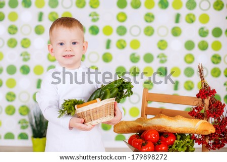 small child in an apron with vegetables and herbs. cucumbers. cook. kitchen, boy chef - stock photo
