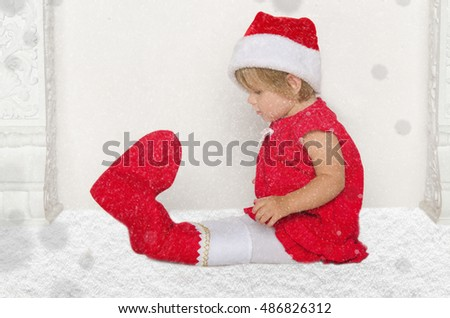 Small child in Santa suit sitting on floor with snow studio shot
