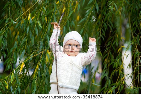 Small child in the park. Looks in a camera. - stock photo