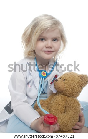 small child is dressed as a doctor, the child is sitting on the ground and is holding a teddy bear in her hand