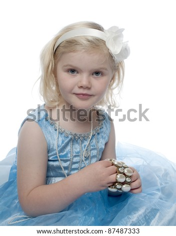 Small child is looking directly at camera and is smiling. She is dressed as a princess.