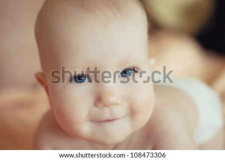 small child is sitting on an orange towel - stock photo