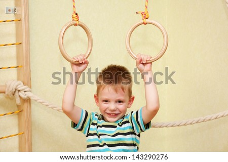 Small child playing sports at sport center. Kid exercising on gymnastic rings - stock photo