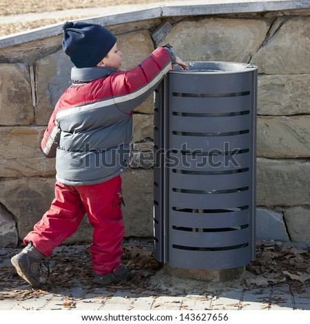 Small child putting a waste or litter in a street rubbish can or bin. - stock photo