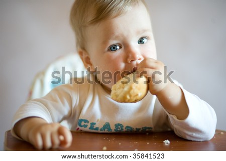 Small child sits at a table and eats bread