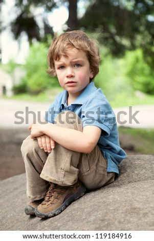 Small child sits on stone in park - stock photo