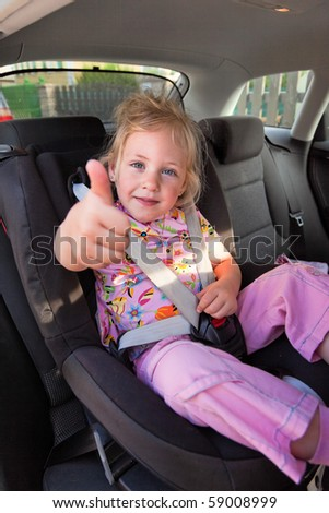 Small child sitting in a car seat in the car
