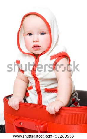 small child sitting in a red suitcase on white background