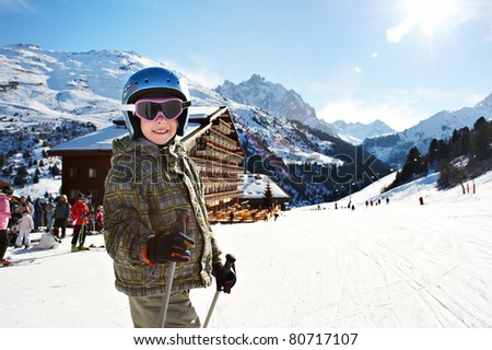 Small child skiing on snow slope in resort