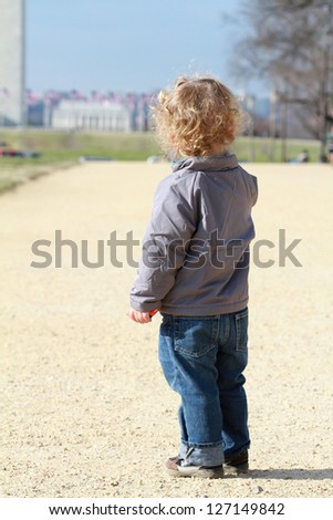 Small child, toddler boy on the Mall in Washington DC, looking at the Washington Monument