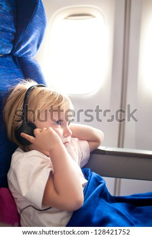 small child with headphones in the plane - stock photo
