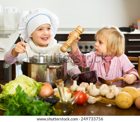 Small children cooking food in the kitchen indoors - stock photo