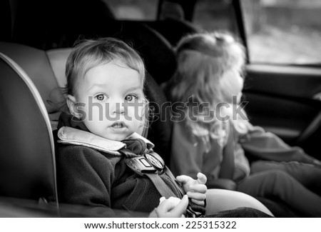 small children in car seats in the car ( black and white ) - stock photo