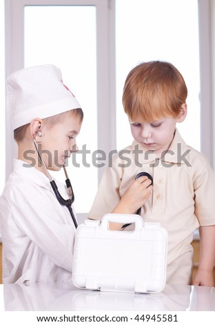 Small children play hospital and doctor - stock photo