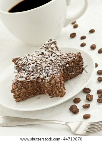 Small chocolate star-shaped cake and coffee cup. Shallow dof.