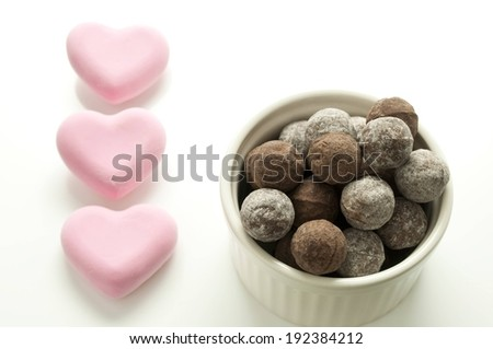 Small chocolates filling a white bowl with pink candy hearts at the side. - stock photo