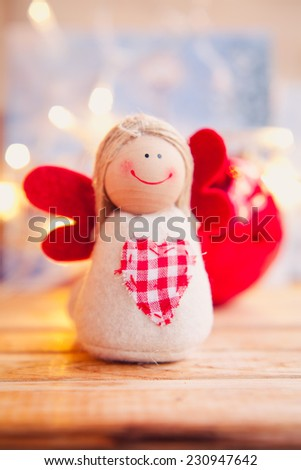 Small christmas angel with red wings. Family and child, christmas gifts.Christmas decoration. Colorful window in the city during winter.  - stock photo