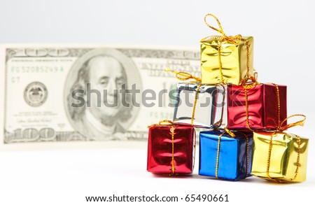 Small Christmas gifts with $100 bill on background - stock photo