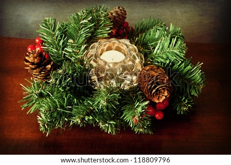 Small Christmas wreath with a candle in glass on grunge texture - stock photo