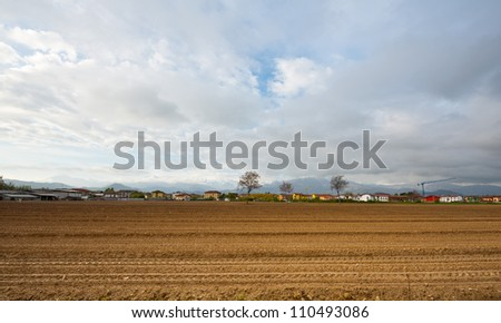 Small City in Piedmont on the Background of Snow-capped Alps - stock photo
