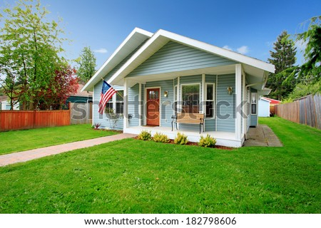 Small clapboard siding house. View of porch with bench and walkway