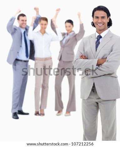 Small close-up of a businessman smiling and crossing his arms with enthusiastic people behind him against white background - stock photo