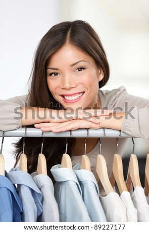 Small clothing shop owner. Portrait closeup of young woman clothes store business owner standing in her shop behind clothes rack smiling happy. Beautiful smiling mixed race Asian Caucasian young woman