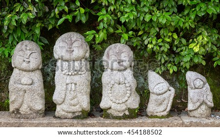 Small coins are left at a row of ancient temple statues of Buddhist monks. These very small statues sit on pavement outside the Arashiyama Temple in Kyoto, Japan. - stock photo