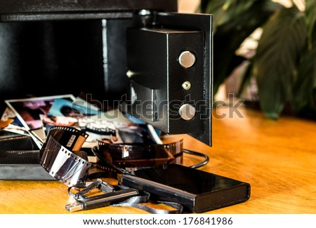 small collection of photos, film and hard drives spilling out of a safe onto a table/ Treasures of a safe/  - stock photo